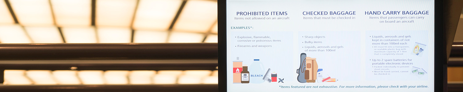 Photo of screen at check-in counter showing list of items that should and should not be packed in luggage.